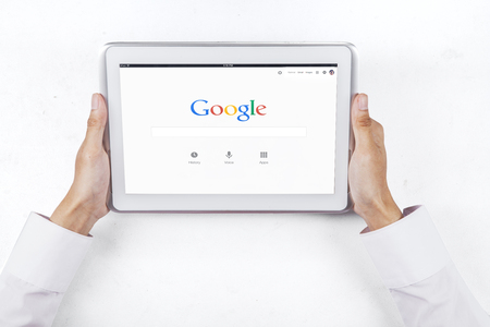 google chrome: JAKARTA, SEPTEMBER 09, 2015: Image of businessperson hands holding digital tablet with google homepage on the screen