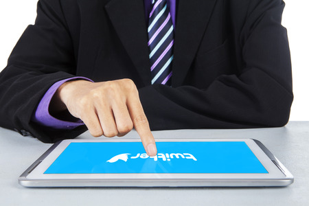 business marketing: JAKARTA, SEPTEMBER 09, 2015: Closeup of worker hands touching the logo of twitter site on the digital tablet computer