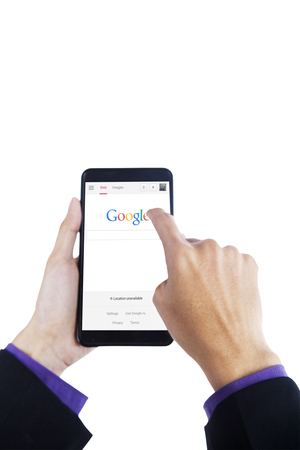 google chrome: JAKARTA, SEPTEMBER 10, 2015: Image of worker hands using smartphone with google search engine on the screen