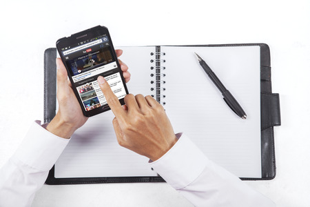 JAKARTA, SEPTEMBER 08, 2015: Photo of businessman hand using smartphone to open youtube online Editorial