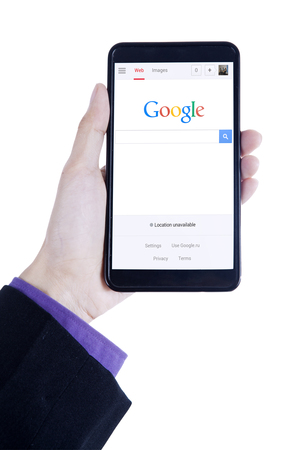 google chrome: JAKARTA, SEPTEMBER 08, 2015: Closeup of businessman hand using a smartphone to open google homepage