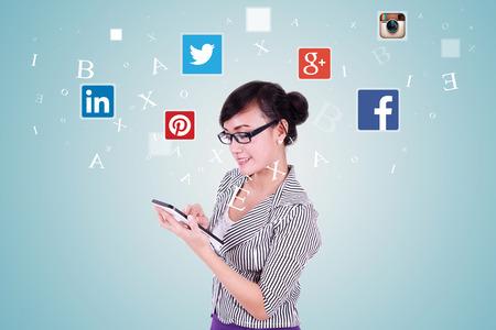 JAKARTA, 8 september 2015: Beeld van de jonge Aziatische vrouw bedrijf en met behulp van digitale tablet met sociale media iconen: Facebook, Google Plus, Instagram, Twitter, Pinterest en LinkedIn