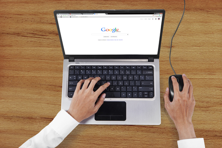 screen search: JAKARTA, SEPTEMBER 08, 2015: Image of worker hands using laptop to open google search web page