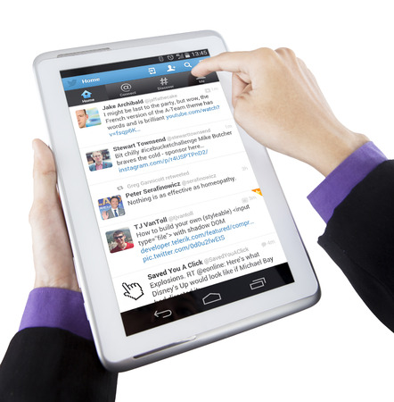 JAKARTA, SEPTEMBER 08, 2015: Closeup of businessman hand touching tablet screen with twitter profile