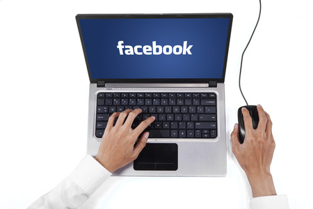 using computer: JAKARTA, SEPTEMBER 08, 2015: Image of entrepreneur hands working on the laptop computer with facebook logo on the screen Editorial