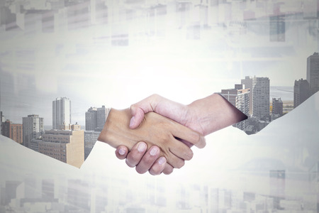 Double exposure of two businesspeople shaking hands with office building background