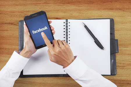 JAKARTA, SEPTEMBER 08, 2015: Image of businessman hand touching facebook logo on the mobile phone screen while working with notebook on the table