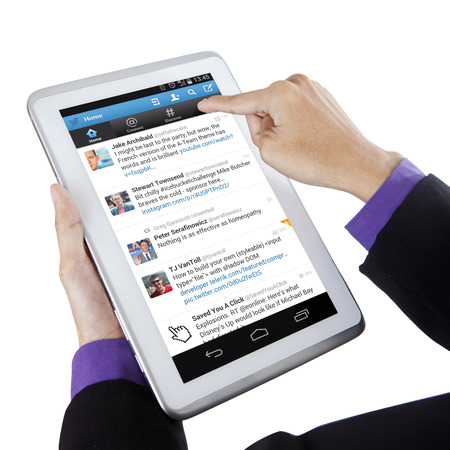 microblogging: JAKARTA, SEPTEMBER 10, 2015: Closeup of businessperson using digital tablet computer to open twitter profile