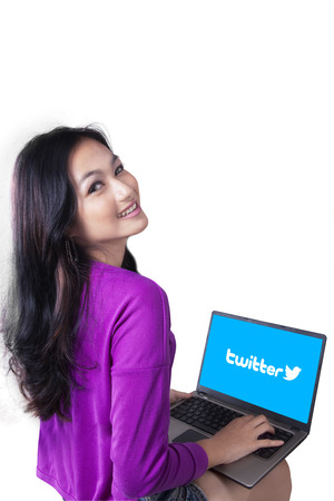 microblogging: JAKARTA, SEPTEMBER 07, 2015: Teenage girl smiling at the camera while using laptop computer to access social media site of twitter