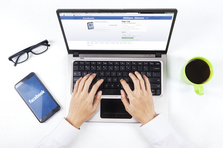 microblogging: JAKARTA, SEPTEMBER 09, 2015: Photo of businessman hands opening facebook webpage with facebook logo on the smartphone screen Editorial