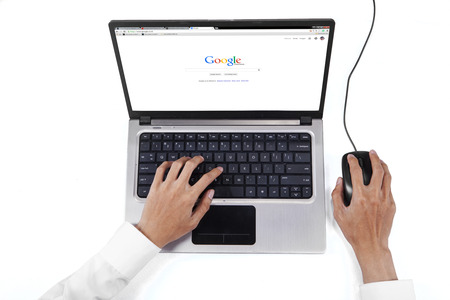 pc screen: JAKARTA, SEPTEMBER 08, 2015: Closeup of businessman hands working with laptop while using google homepage on the laptop screen Editorial