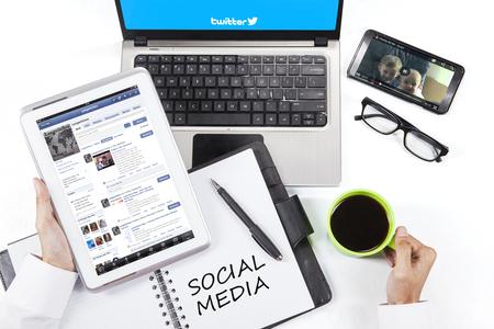 trabajo social: YAKARTA, 09 de septiembre de 2015: El hombre de negocios que usa la tableta, ordenador portátil, teléfono inteligente y acceder a los sitios de medios sociales de Facebook, Twitter y YouTube Editorial