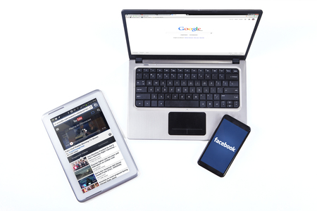 JAKARTA, SEPTEMBER 08, 2015: Closeup of laptop computer with google homepage, digital tablet with youtube webpage, and smartphone with facebook logo
