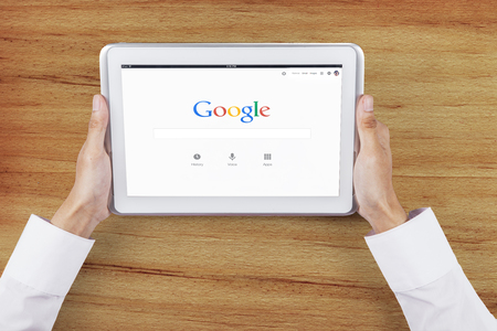 google chrome: JAKARTA, SEPTEMBER 09, 2015: Closeup of businessman hands holding digital tablet with google logo on the screen