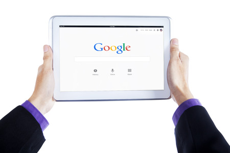 google chrome: JAKARTA, SEPTEMBER 09, 2015: Image of entrepreneur hands holding tablet computer with google homepage on the screen Editorial