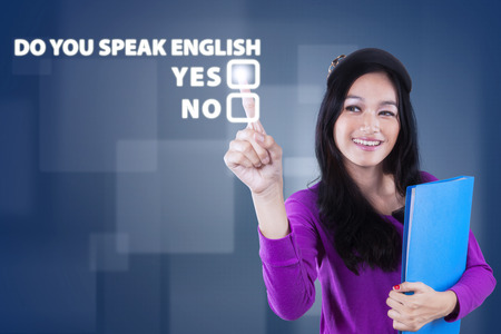 Image of beautiful teenage girl learn english speaking and touching a text of Do You Speak English? Reklamní fotografie