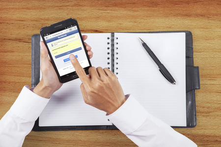 signup: JAKARTA, SEPTEMBER 08, 2015: Image of worker hands touching a smartphone screen and login the facebook site Editorial