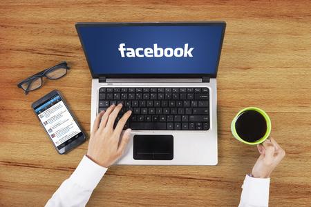 JAKARTA, 9 september 2015: Close-up van de facebook-logo op de laptop met een twitter-profiel op de mobiel met de werknemer handen bedrijf koffie