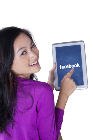 microblogging: JAKARTA, SEPTEMBER 07, 2015: Image of attractive teenage girl smiling at the camera while holding a digital tablet and showing facebook logo on the screen Editorial