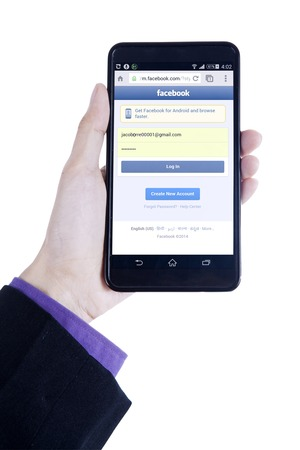 logo samsung: JAKARTA, SEPTEMBER 08, 2015: Closeup of businessman hand using a smartphone to open facebook login page biên tập