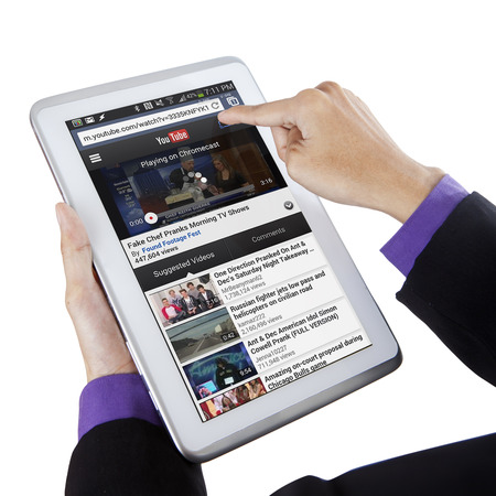 JAKARTA, SEPTEMBER 10, 2015: Closeup of businessperson hands opening youtube online with digital tablet computer