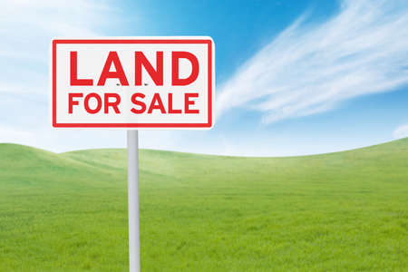 house sale: Real estate concept. Land For Sale signboard on the meadow under clear sky Stock Photo