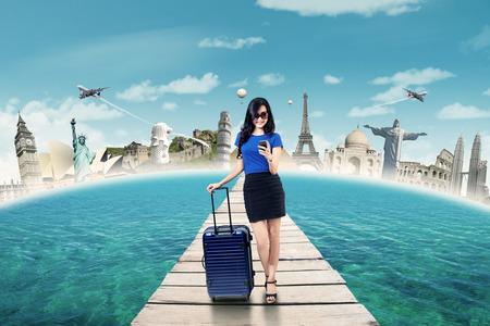 Mooie vrouwelijke toerist die zich op de steiger, terwijl draagtas en het verzenden van berichten met mobiele telefoon