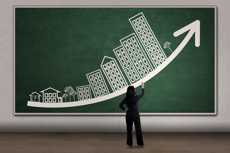 Young businesswoman drawing business property chart with arrow and house picture on the blackboard