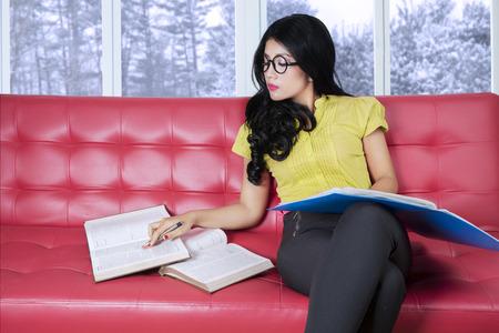 persona leyendo: Mujer joven atractiva con ropa casual, sentado en el sofá, mientras que la lectura de libros con el fondo del invierno en la ventana
