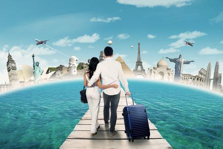 橋の上を歩いて、世界記念碑で新婚旅行に行く 2 つの観光客の後姿 写真素材