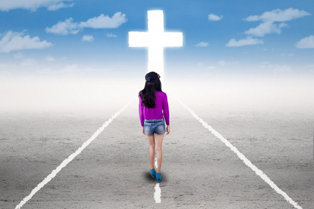 way: Awareness teenage girl walking on the road and follow a cross
