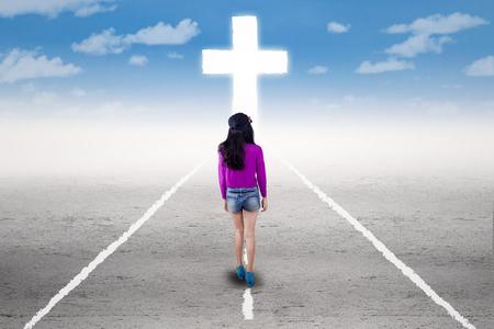 obediencia: Conciencia adolescente caminando por la carretera y seguir una cruz