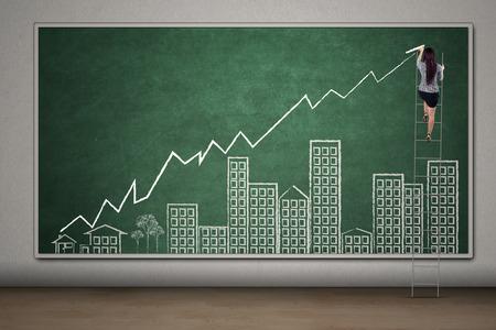 incremento: Empresario de sexo femenino joven con escalera para dibujar un gráfico de bienes raíces con la flecha y la construcción de imágenes en la pizarra Foto de archivo
