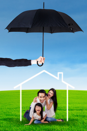 family life: Portrait of happy family playing together on the meadow and protected by umbrella Stock Photo