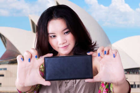 chinese opera: Pretty female teenager enjoy holiday in Sydney and use a mobile phone to take selfie at Opera House Stock Photo