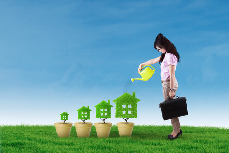 water in can: Photo of asian businesswoman using watering can to give water on the tree house. Real estate investment concept