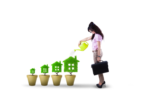 finance concept: Photo of young female entrepreneur giving water into tree house with a watering can. Housing and real estate investment