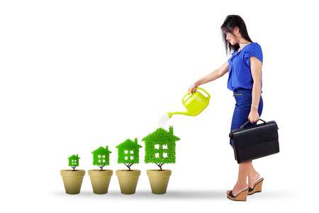 real estate investment: Image of young businesswoman using watering can to pour water into tree house. Green real estate investment concept Stock Photo