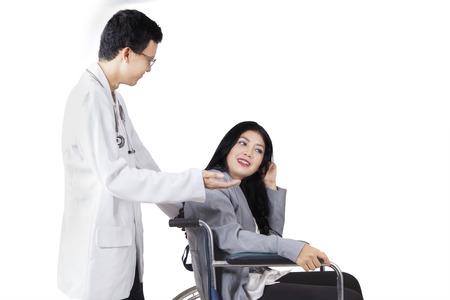 empujando: Doctor de sexo masculino joven que habla con el paciente discapacitado se sienta en la silla de ruedas, aislado en fondo blanco