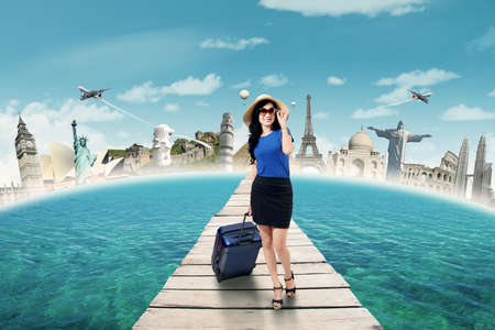 happy asian people: Image of beautiful female tourist walking on the bridge while carrying luggage and wearing sunglasses