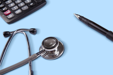 fee: Photo of stethoscope with calculator and pen on the blue background. Concept of medical fee Stock Photo