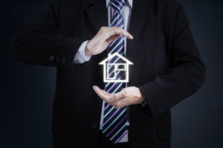 values: Image of businessman hand protecting house icon. Property insurance concept