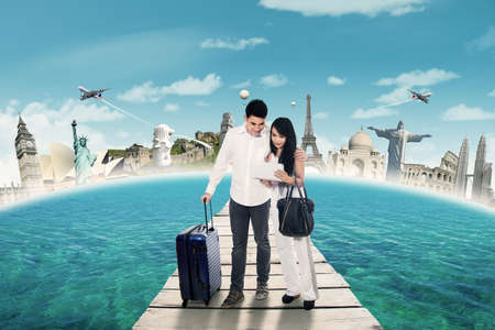 luggage travel: Photo of two asian travelers standing on the jetty while carrying bag and finding the destinations on the tablet