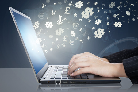 Image of businesswoman hands working on the laptop computer with currency symbols. Making money online concept