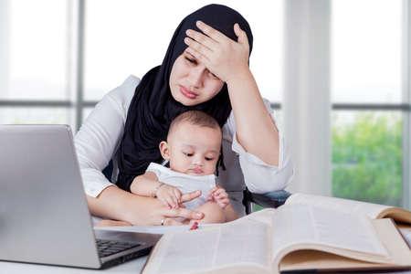 madre y bebe: Empresaria joven llevando a su bebé mientras se trabaja en la oficina con el ordenador portátil y los libros