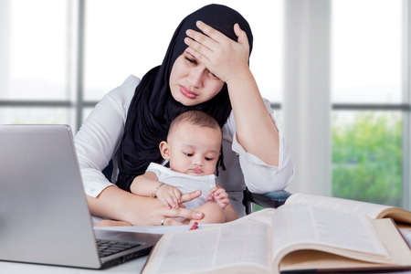 mother baby: Young businesswoman carrying her baby while working in the office with laptop and books