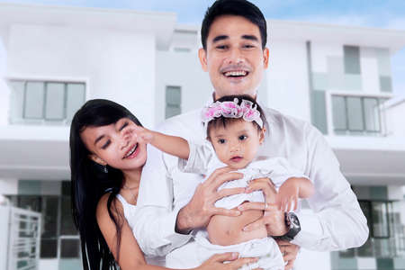 front of: Happiness young asian family standing in front of new home Stock Photo