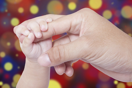 infant hand: Closeup of infant hand holds father finger, symbolizing love and family, shot with light  glitter background