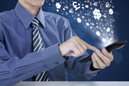 icon phone: Photo of male entrepreneur hands holding mobile phone with currency signs. Making money online concept Stock Photo
