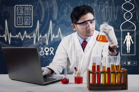 pharmacy equipment: Portrait of male chemist wearing lab coat, typing on laptop and looking at chemical glassware